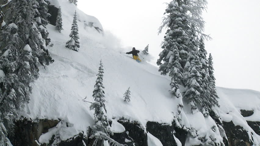 Skier carves down a steep run up, before a huge drop, slow motion