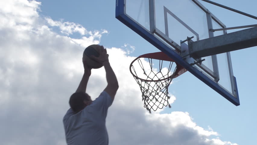 Spectacular Low Angle Rearview Shot Of Professional Basketball Player Scoring A Basket By Alley-Oop And Hanging On The Hoop