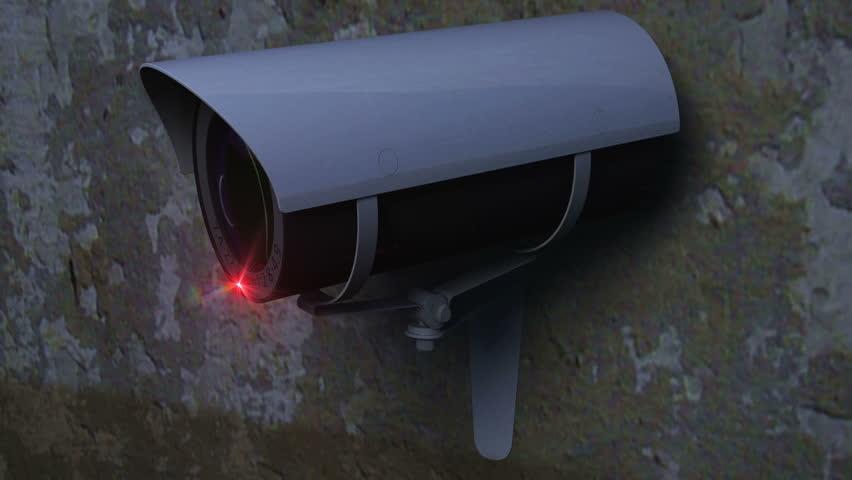 Close up of CCTV camera performing sweep loop against grunge type wall.