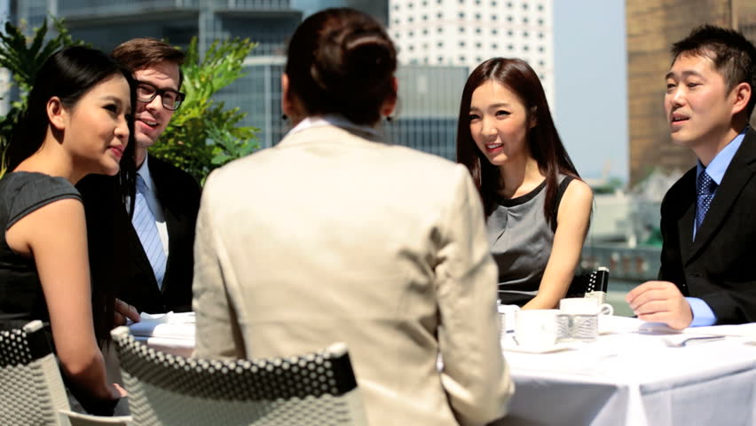 Group male female Asian Chinese Caucasian business people meeting drinking coffee city rooftop restaurant