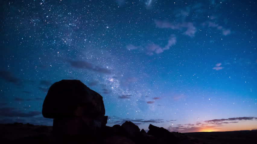 Timelapse of the rising Milky Way with silhouette rocks in the foreground with scattered clouds, starting at blue hour through the night until blue hour before sunrise, shot blowing out at the end.
