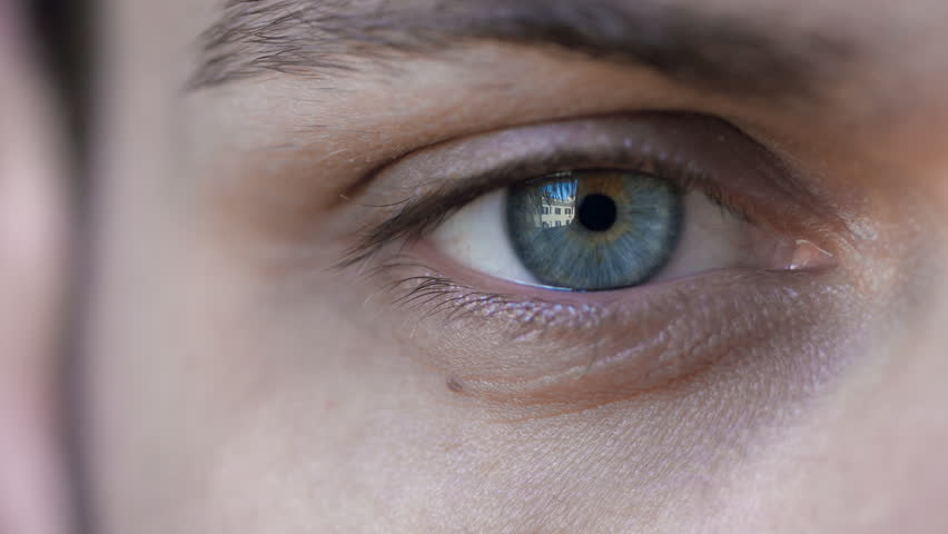 intense gaze: blue eye in macro 4k footage of young handsome man