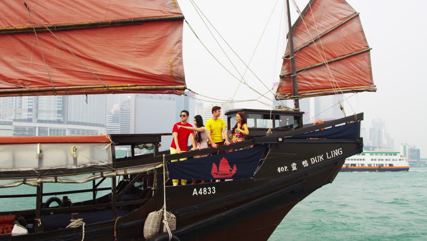 Distant view young Caucasian Asian Chinese people vacation enjoying harbor sightseeing tour Hong Kong Island sailing aboard traditional designed Chinese junk shot on RED EPIC