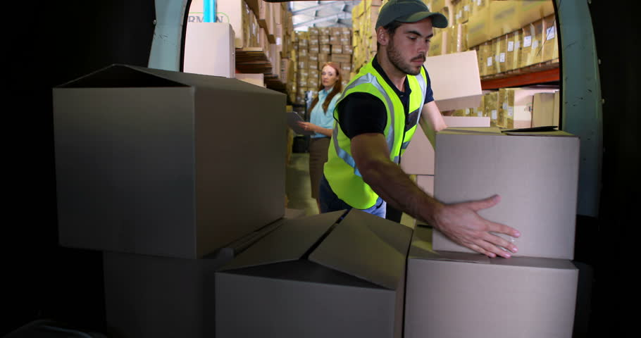Delivery driver loading his van with boxes in a large warehouse - 4K stock footage clip