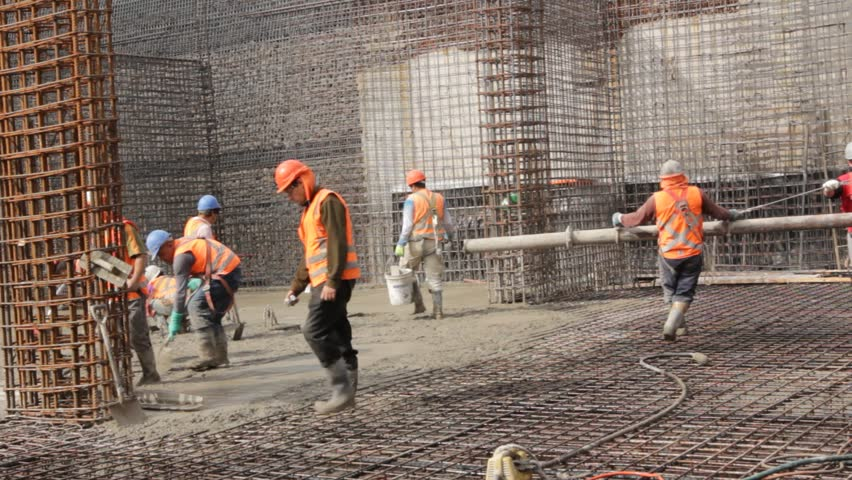 SANTIAGO, CHILE - CONSTRUCTION SITE - A group of construction workers carry a large tube used to pour cement across the floor of a reinforced concrete building while other workers spread wet cement.