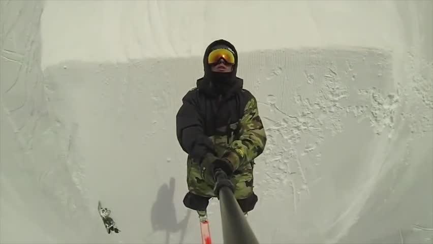A skier catches air and does spins before losing balance and falling on the hard snowy surface