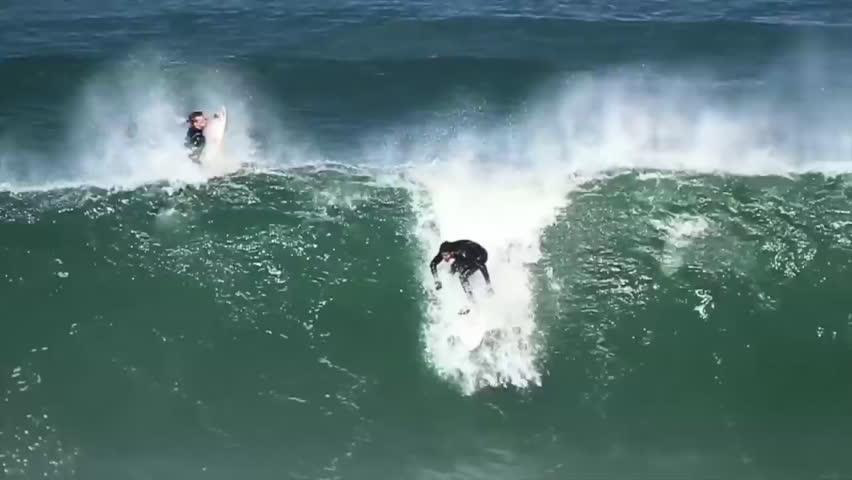 A surfer rides the tube of a big wave and emerges out of it