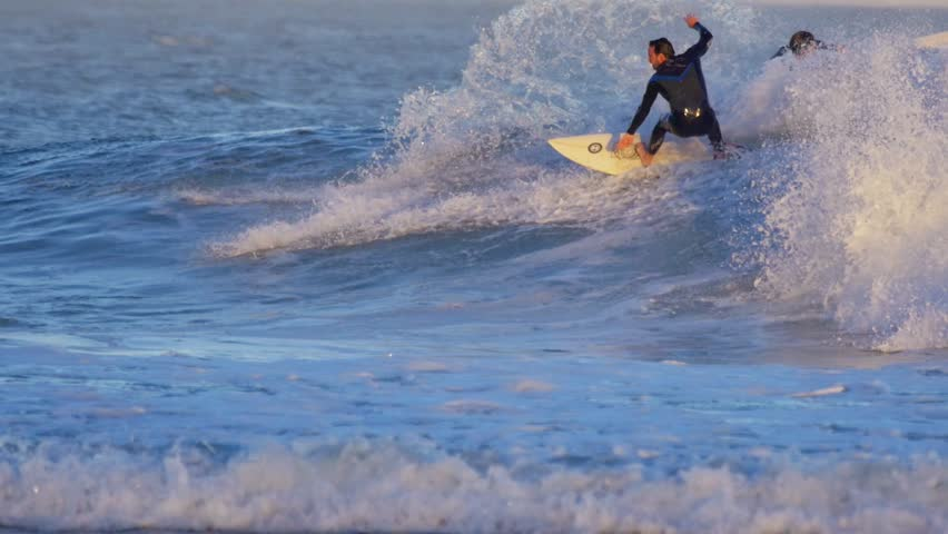 MALIBU, CALIFORNIA - August 28, 2014: Surfers surfing hurricane Marie waves at sunset. Slow motion.