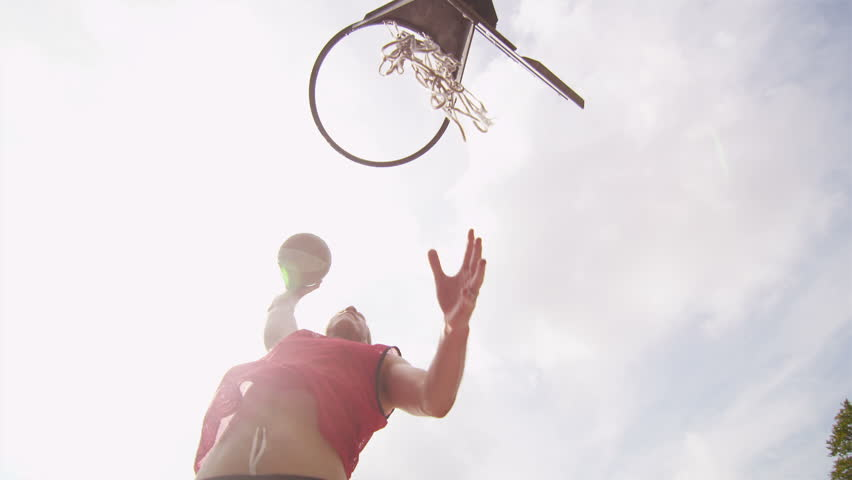 Male basketball player slam dunking on an outdoor basketball court on a sunny day, shot on RED EPIC - HD stock footage clip