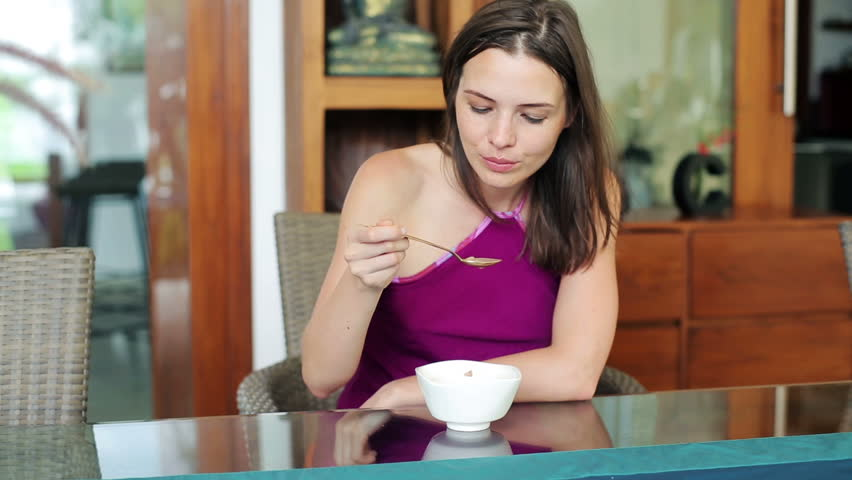 Hungry woman eating tasty soup by dinner table