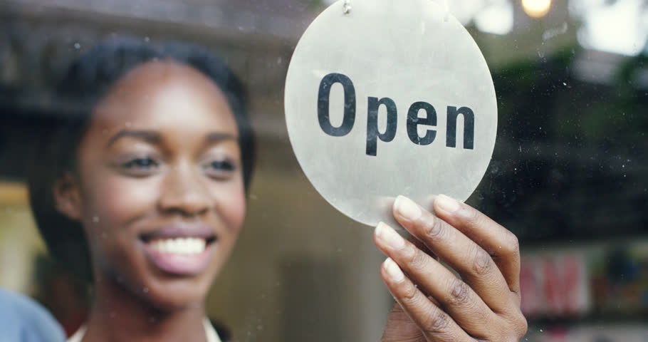 Small business owner turning over open sign
