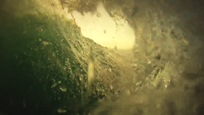 A wave barrels in slow motion during sunset, view from inside the tube