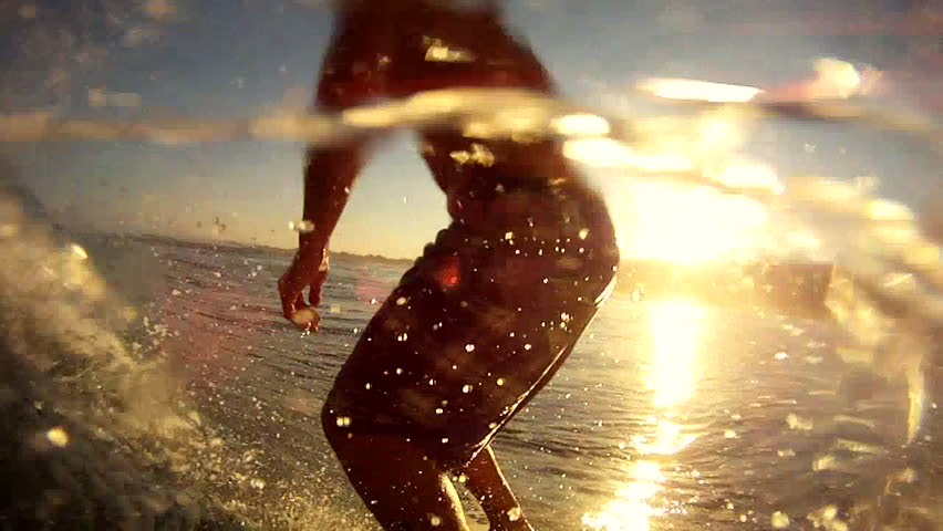 A surfer gets barreled during sunset in slow motion, pov
