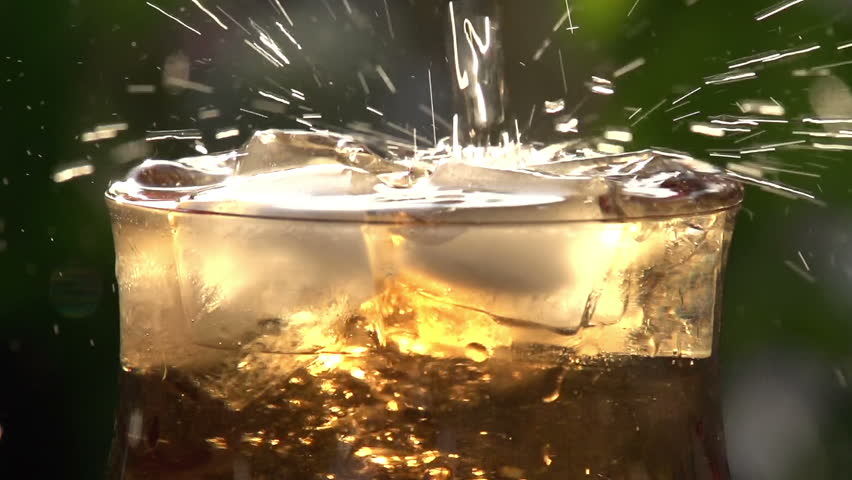 Stream of Champagne in a Glass with Ice. In a glass of sweet sparkling wine with ice cubes. A stream of champagne fills the glass over the edge and creating a beautiful foam and spray - HD stock footage clip