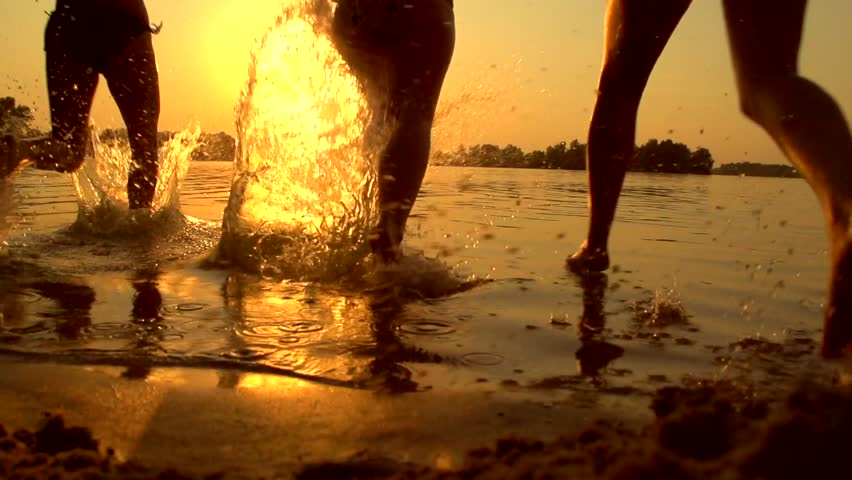 Group of happy girls running and playing in water at the beach on sunset. Beauty and joyful teenager friends having fun, dancing, spraying over summer sunset. Beach party. Sun flare. Slow motion 1080p