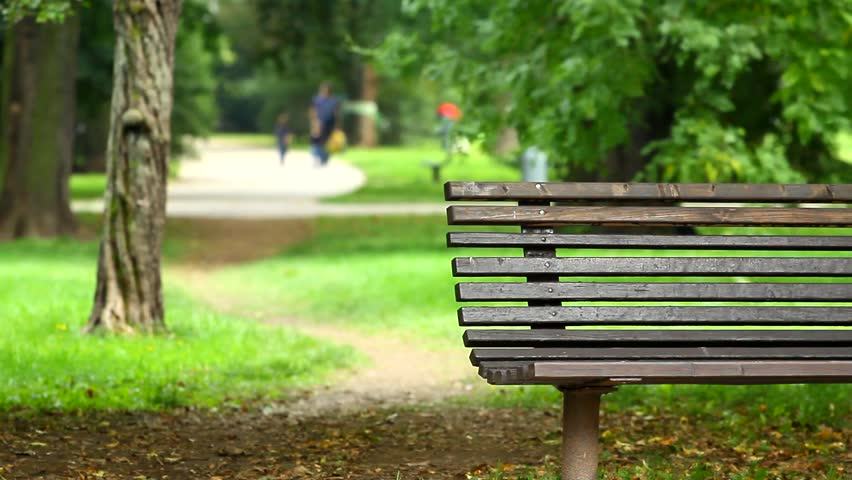 empty wooden park bench in a late summer park, unrecognizable people in the background