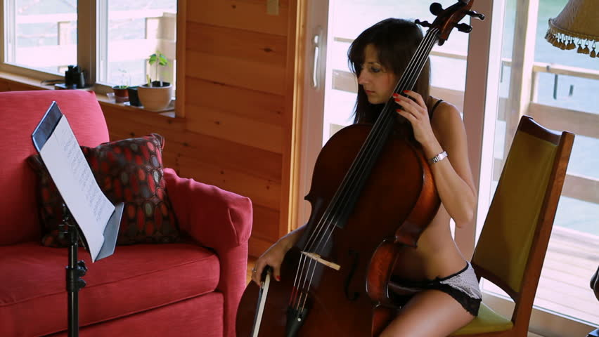A beautiful cellist studies the music in detail.   - HD stock video clip