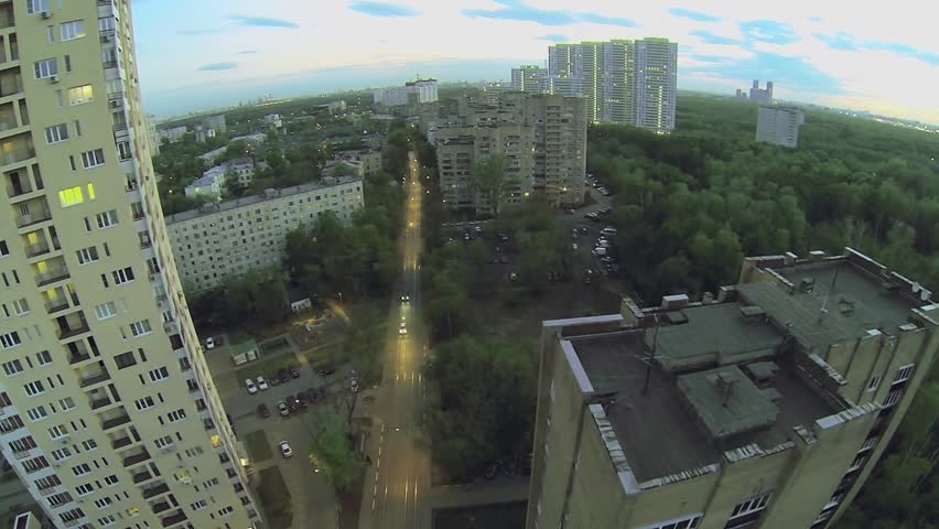 City outskirts with car ride by street near tramway line at evening. Aerial view - HD stock video clip