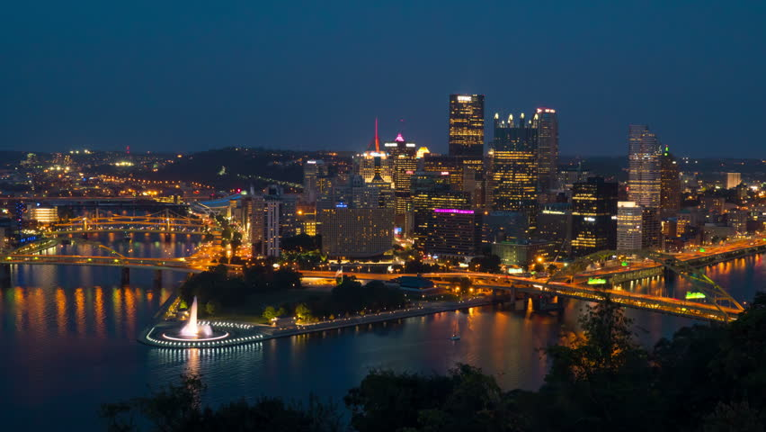 (Time-lapse) Night falls on the downtown area of Pittsburgh, Pennsylvania including the skyline, bridges, and Point State Park at the confluence of the Allegheny and Monongahela Rivers. - 4K stock video clip