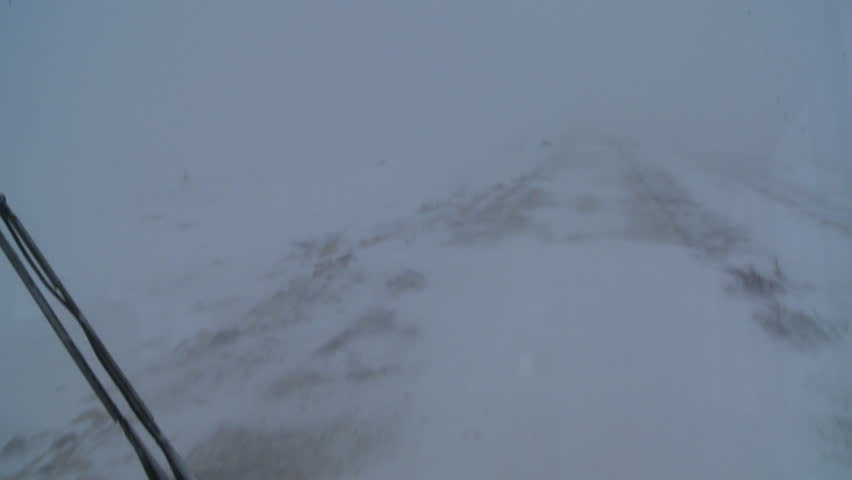 CHURCHILL, MANITOBA, CANADA - CIRCA 2014 - Point of view shot from a tundra vehicle of frozen tundra and barely visible road in the Arctic during an intense blizzard.