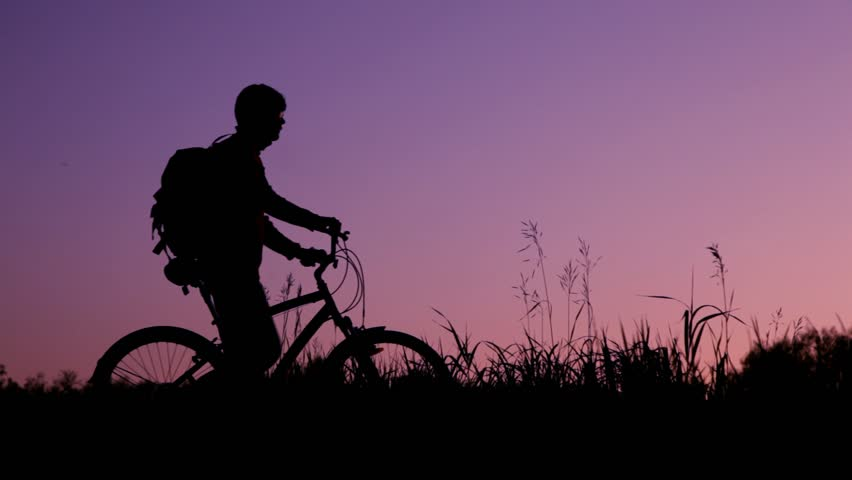silhouettes of two bicyclists with knapsacks against sunset sky