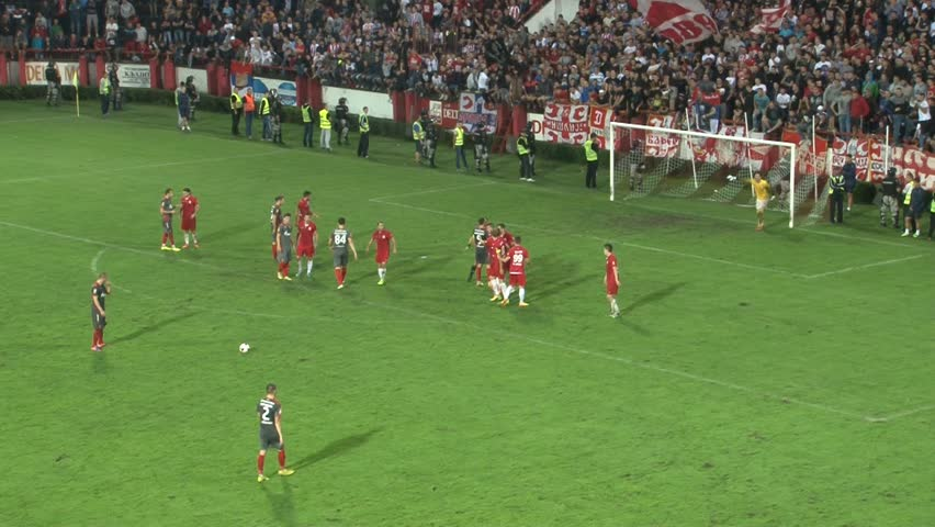 Srbija,Krusevac,2014. FC Napredak-FC Crvena Zvezda. Football. Soccer. Fantastically executed free kick. Ball hits the crossbar. Two football (soccer) clubs playing derby match under reflectors. 25 fps