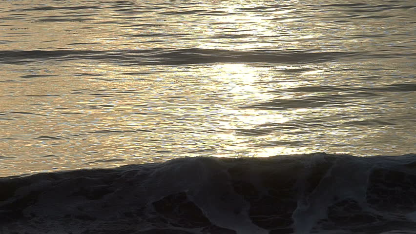 An ocean wave breaks on the beach in slow motion during sunset in California, USA.