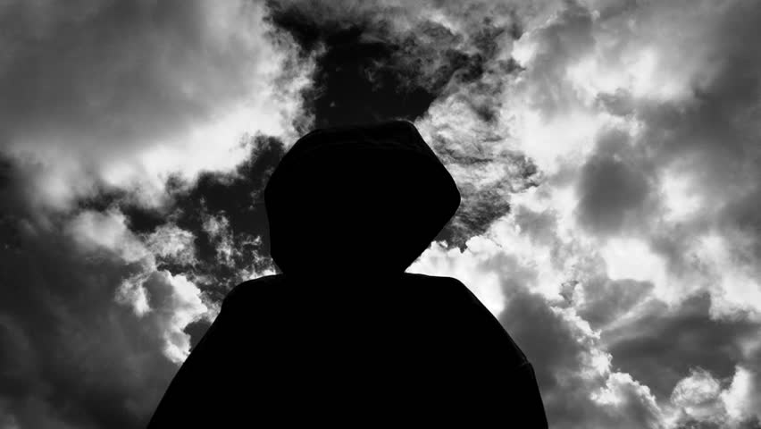 Dark and mysterious silhouetted figure raises hands and attacks camera, black and white treated.