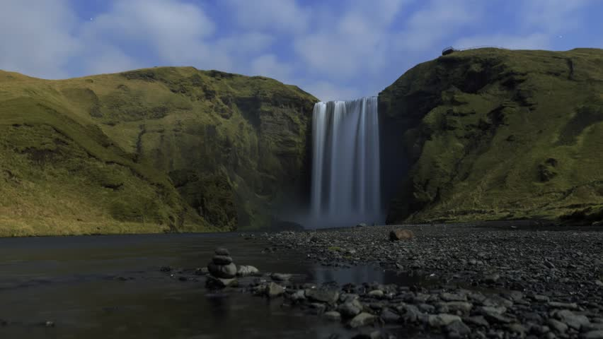 Skógafoss / Skogafoss waterfall timelapse at night with stars, clouds, and rocks.