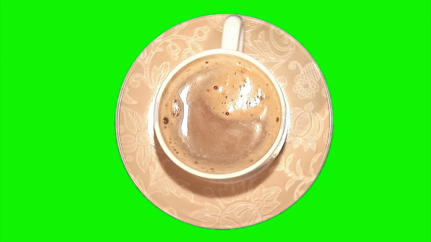 Cappuccino with the scum rotating in the small porcelain coffee cup on the saucer (top shot, green screen, loop)