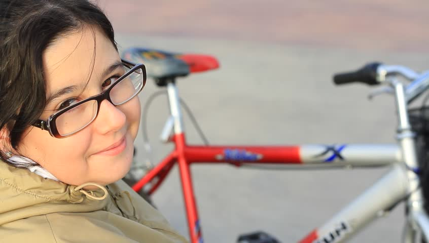 Girl wearing glasses talking in front of her bicycle