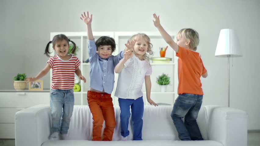 Real time video turning into slow motion of four little friends having fun leaping on the sofa - HD stock video clip