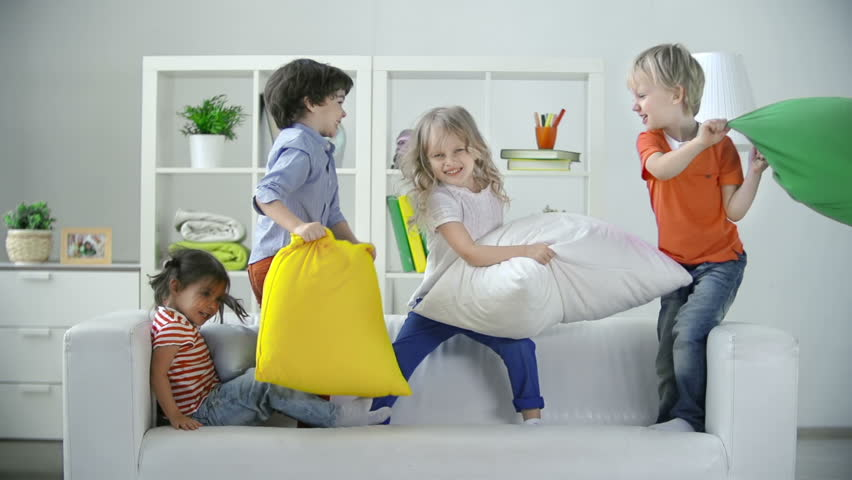 Four kids playing on sofa pillow fighting  - HD stock video clip