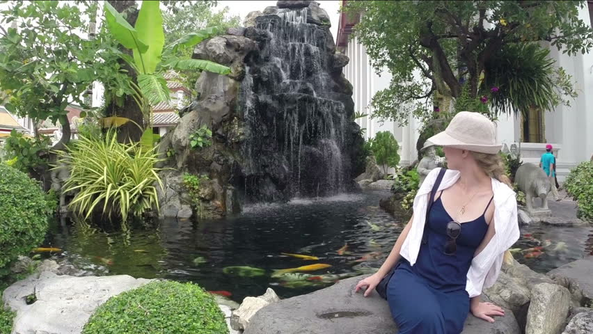 Young beauty woman sitting at a fountain.  Thailand