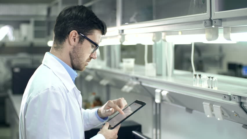 Laboratory worker checking the contents of glassware and inputting data to digital tablet