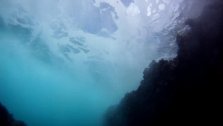 Swimming underwater beneath the ocean waves in Hawaii.