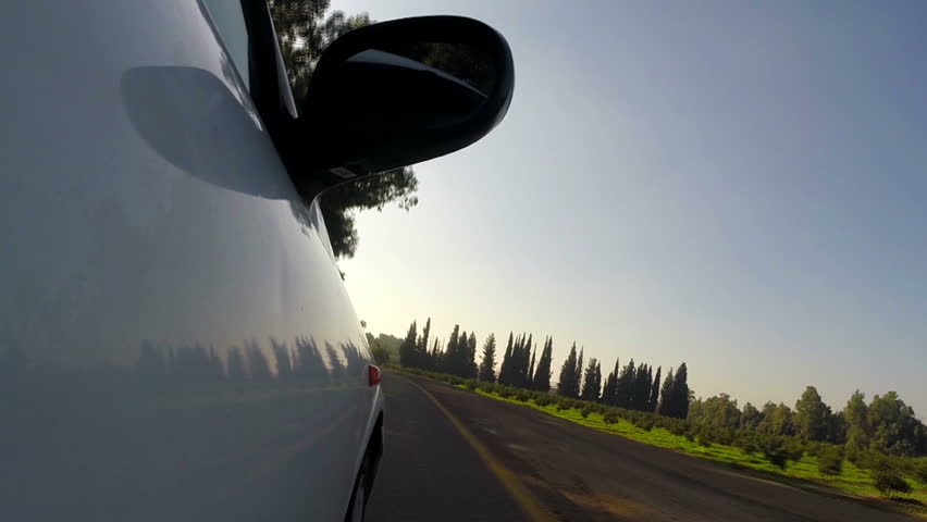 Car on country road. Side view. Blue sky on background