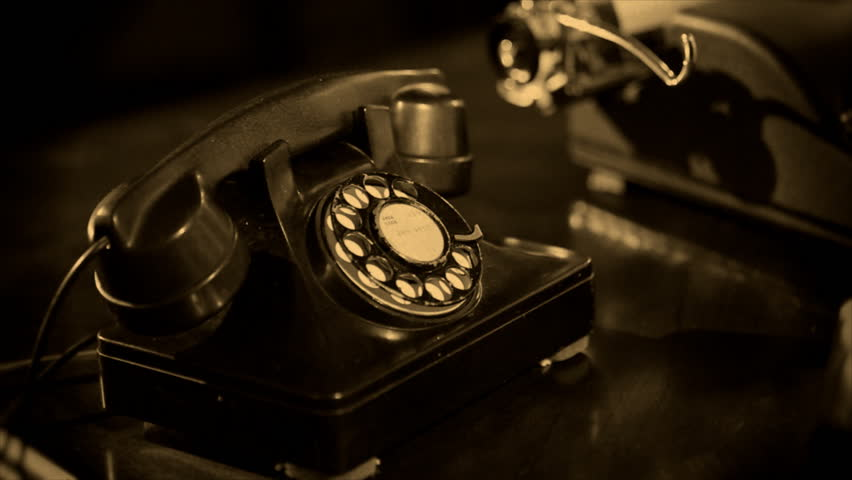 A close up of a man dialing an old vintage 40s style desk telephone. Sepia tone applied for effect. Shallow depth of field.
