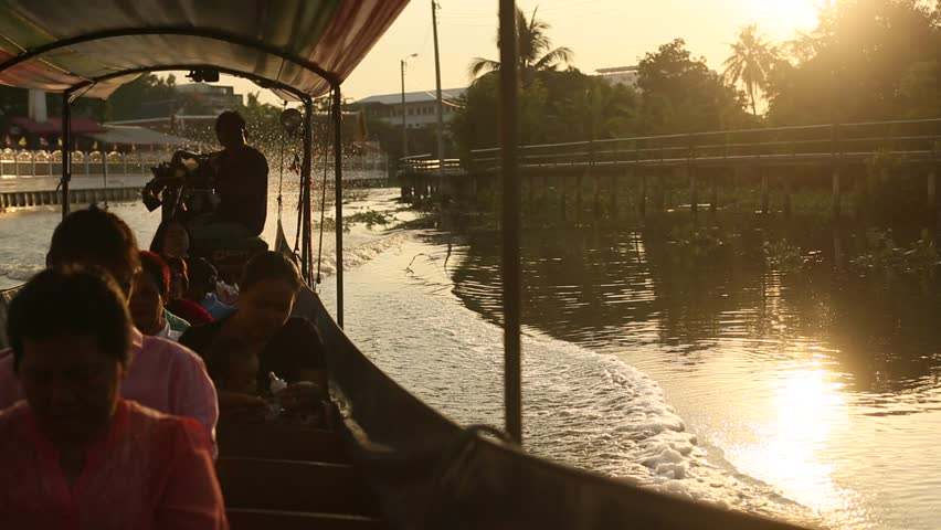 BANGKOK, THAILAND - DEC 19, 2014: A long-tail boat carrying local people passing on the Chao Praya River. Long-tail boats are a cheap form of river transport in the Thai capital.
