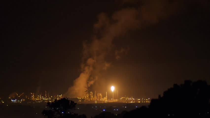 Richmond, California - December, 2014 - Medium shot of flaring from a refinery creating plumes of vapors in the sky.
