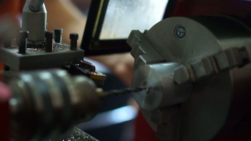 Drilling into metal in lathe setup.Aluminum cylinder is drilled mounted in a spinning metal lathe.