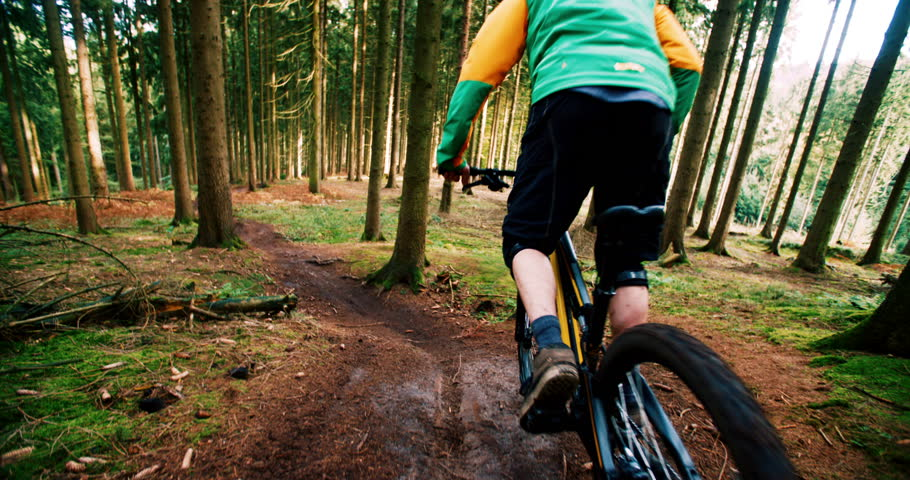 Mountain Biker starting to go downhill in 4k slow motion with MTB in the woods