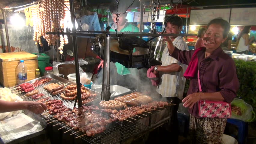 PHUKET, THAILAND - AUGUST 2013: Street food vendor flips various meat kebabs on a grill and customer buys kebabs at background in night food market Phuket, Thailand.