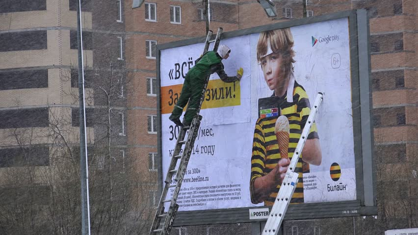 SAINT-PETERSBURG, RUSSIA - JANUARY, 2015: Workers gluing billboard. Shot in 4K (ultra-high definition (UHD)), so you can easily crop, rotate and zoom, without losing quality! Real time.