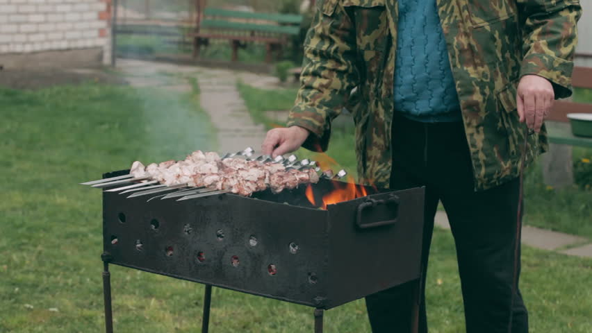 HD: Mature man grilling kebab on BBQ