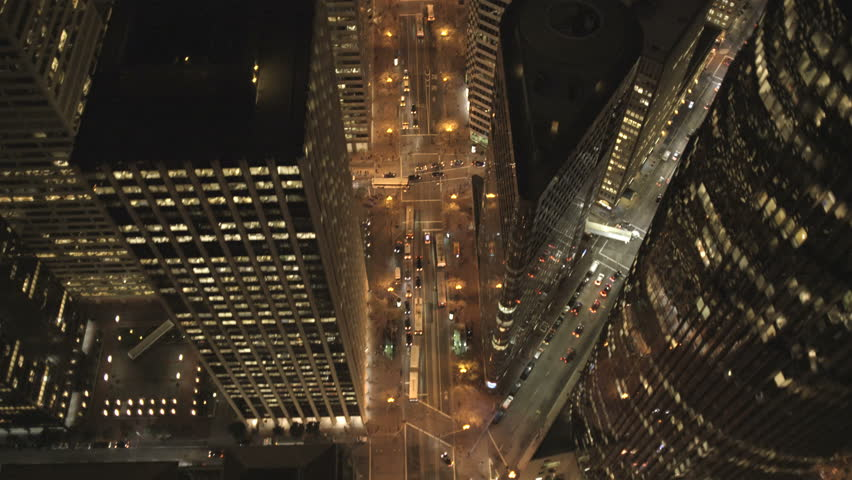 Aerial low level overhead night illuminated rooftop view Downtown Skyscrapers commuter traffic San Francisco California USA 4K