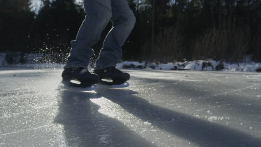 SLOW MOTION CLOSE-UP: Ice skater stopping and spraying - 4K stock video clip