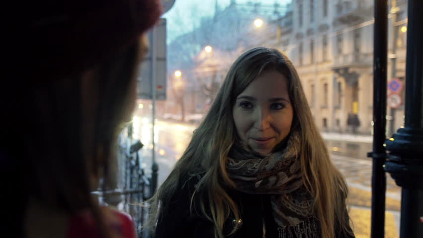 Two girls chatting on the tram stop in the city