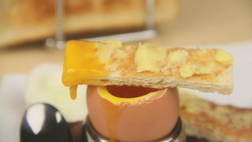 Dipping a piece of toast into the runny yolk of a boiled egg and laying it on the egg to drip.