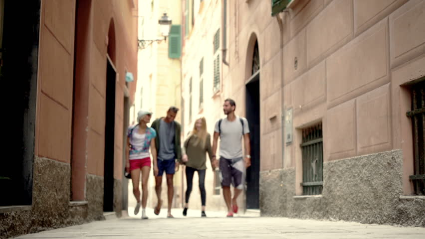 Four multiethnic friends are walking throughout camogli old town center alley in summer day - HD video footage